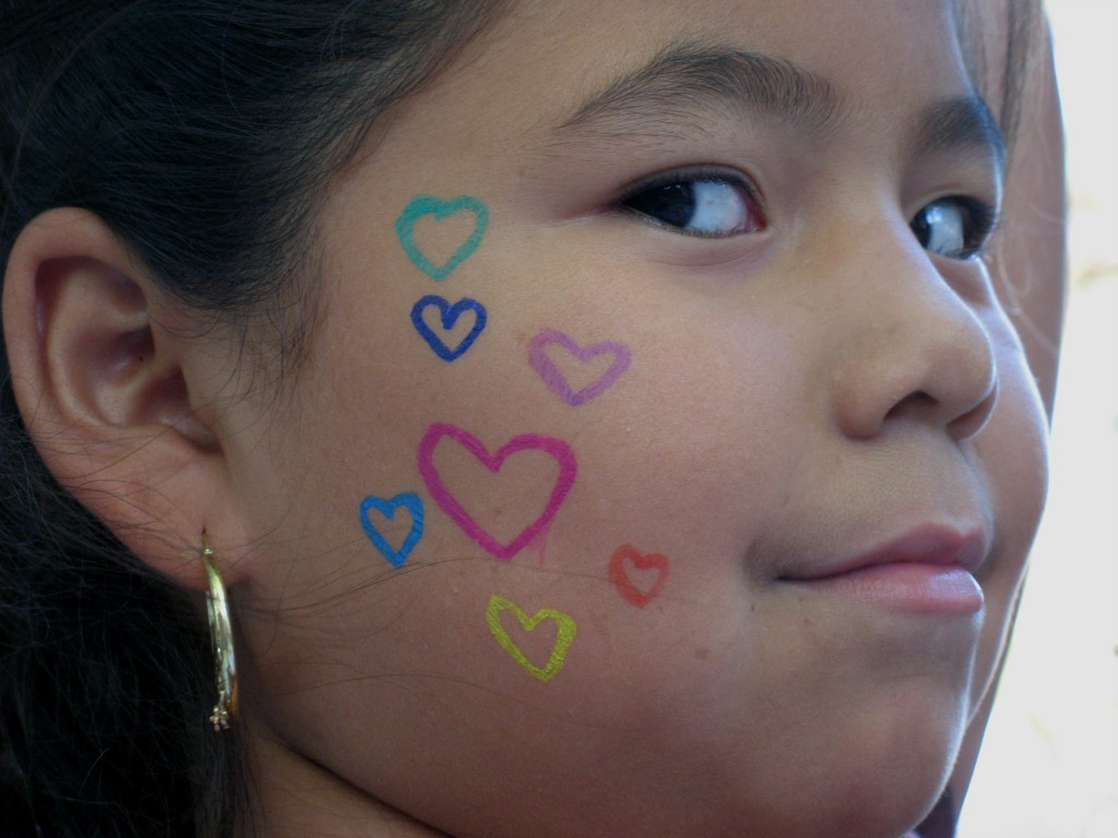 Girl with face painting of hearts on her cheek in celebration of peace.